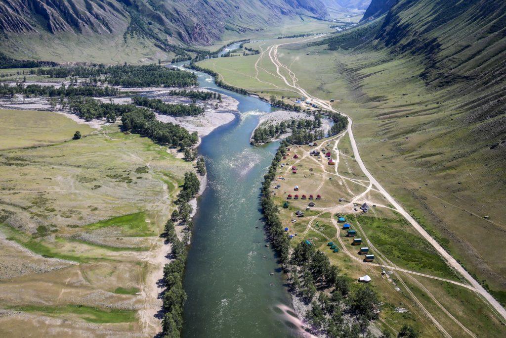 Fluss in einer wunderschönen Tal-Landschaft mit umgebenden Bergen