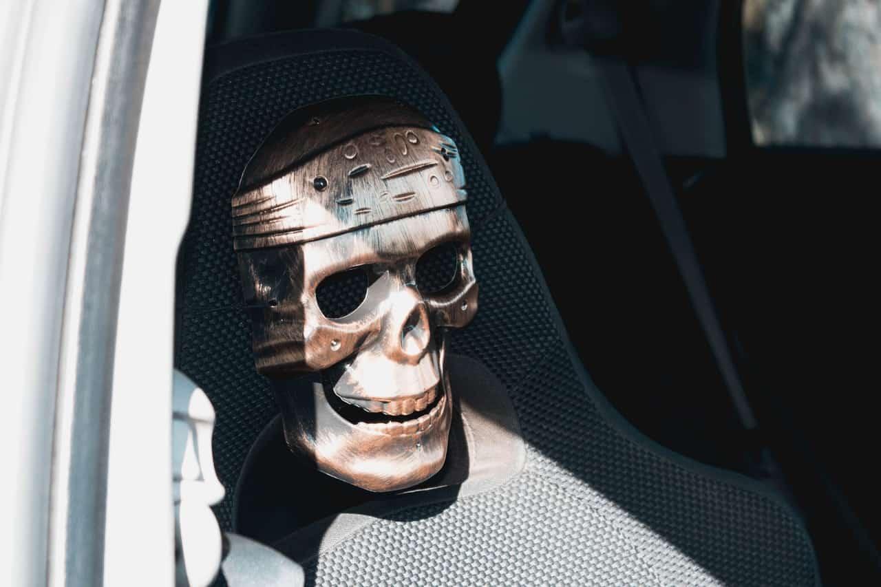 Totenkopfmaske auf dem Auto-Beifahrersitz Gefahr