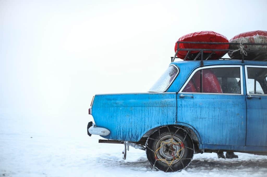 Altes Auto mit Dachgepäck im Winterschnee