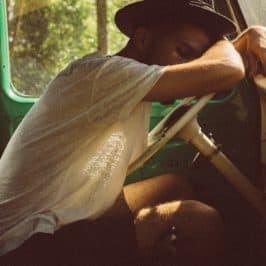 Oldtimer in Mexiko, Brasilien mit schlafendem Mann im Auto auf dem Lenkrad