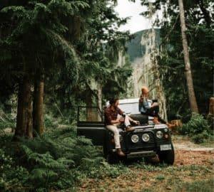 Land Rover Defender mit Personen im Wald