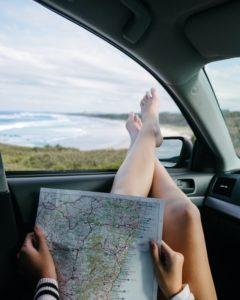 Auto Fahrersitz schlafen, Beine zum Fenster raus mit Blick auf den Stand und Landkarte in der Hand