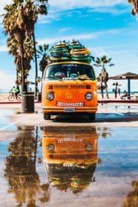 Orangener VW Hippie-Camperbus mit Surfbrettern