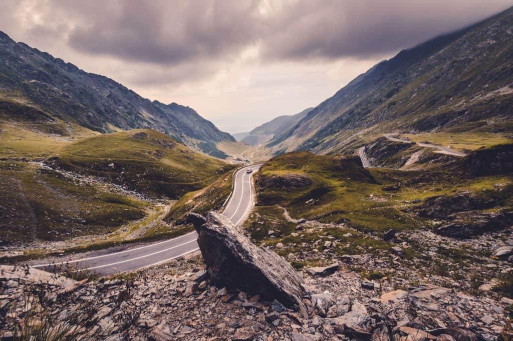 Steinige Straße mit Auto und Bergen