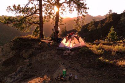 Mit Zelt schlafen im Sonnenuntergang und mit Hund