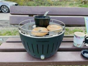 Frühstückszubereitung mit dem Lotusgrill. Rösten von Brötchen und erwärmen von Wasser für den Kaffee beim Camping im Auto