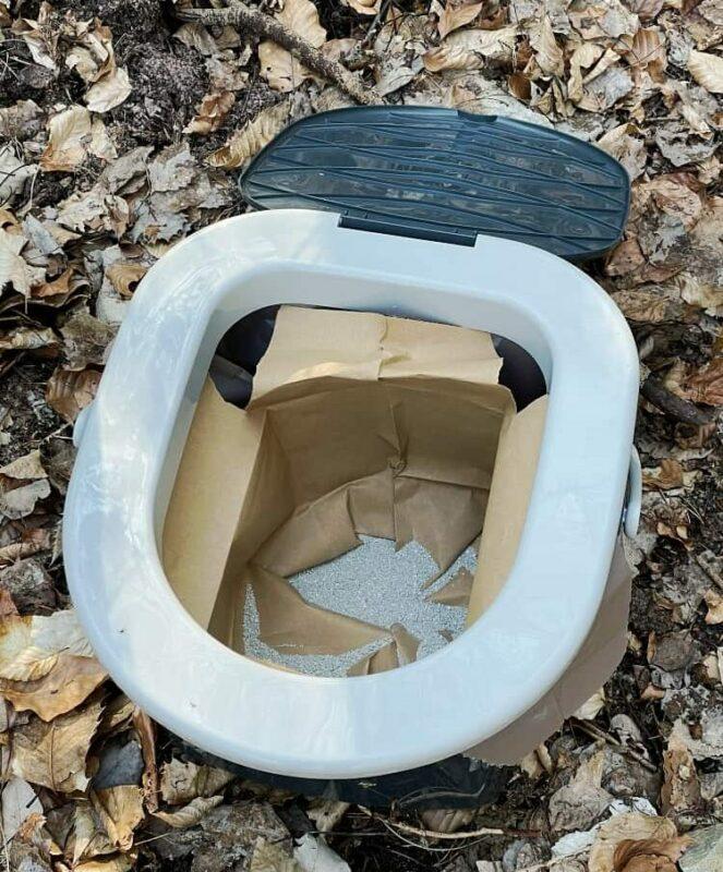 Mobile Campingtoilette mit Papiermüllsack und Katzenstreu im Wald